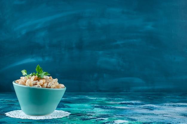 Miska białej fasoli z natką pietruszki na niebieskim stole.
