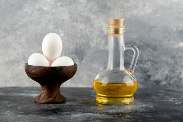 Miska białych jaj i butelka oleju na powierzchni marmuru.