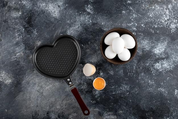 Miska białych jaj i żółtka obok patelni w kształcie serca.