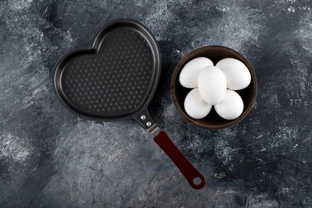 Miska białych jaj obok patelni w kształcie serca.