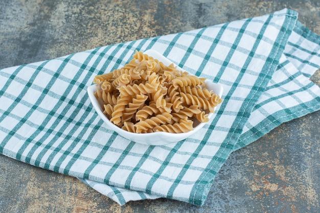 Miska brązowego makaronu fusilli, na ręczniku, na marmurowym tle.