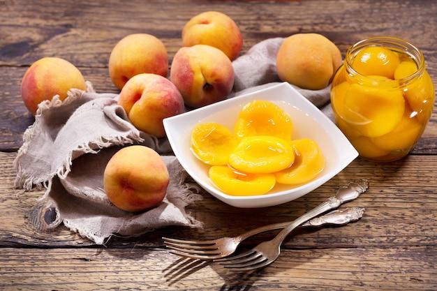 Miska brzoskwiń w puszkach ze świeżymi owocami na drewnianym stole