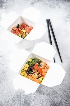 Miska buddy w papierowym pudełku z warzywami, łososiem i tuńczykiem. jedzenie z ulicy na wynos, zabrać.