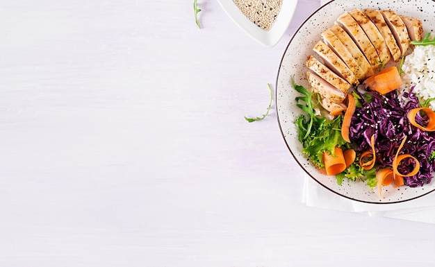Miska buddy z filetem z kurczaka, ryżem, czerwoną kapustą, marchewką, świeżą sałatą i sezamem.