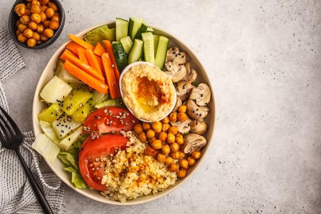 Miska buddy z warzywami, grzybami, bulgur, hummusem i pieczoną ciecierzycą. białe tło, widok z góry.