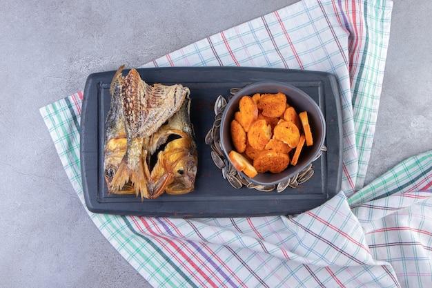 Miska chipsów chlebowych, suszona ryba i nasiona na tacy na ręczniku, na marmurowej powierzchni.