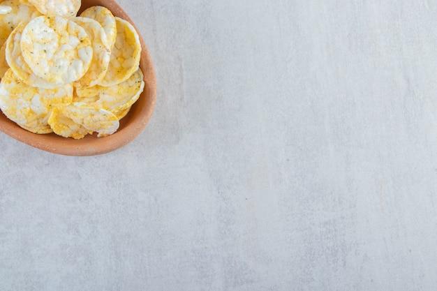 Miska chrupiących ciastek ryżowych pełnoziarnistych na kamieniu.