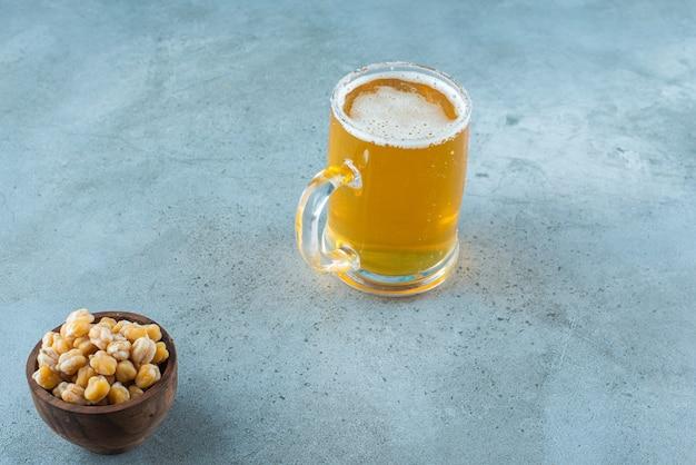 Miska ciecierzycy i szklanka piwa na marmurowym stole.