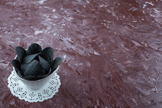 Miska czarnych chipsów ziemniaczanych na podstawce na marmurze.