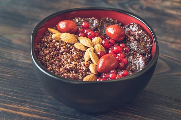 Miska czerwonej komosy ryżowej z orzechami i suszonymi pomidorami i czerwonymi oliwkami