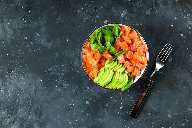 Miska dietetyczna bez węglowodanów keto. szpinak, łosoś, awokado i pomidory w misce na ciemnym tle