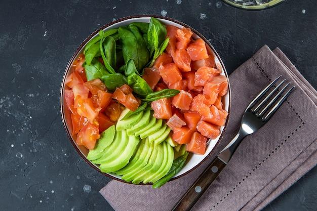 Miska dietetyczna bez węglowodanów keto. szpinak, łosoś, awokado i pomidory w widoku z góry miski.