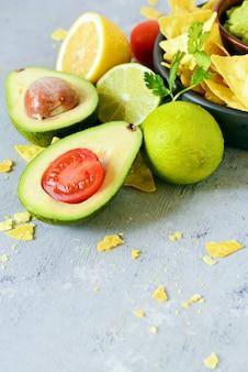 Miska dipu guacamole z nachos kukurydzianym (frytkami) i dodatkami, meksykańskie danie narodowe.