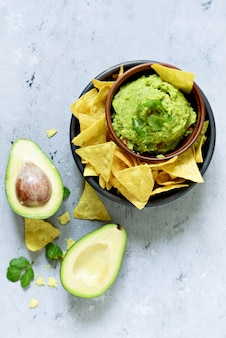 Miska dipu guacamole z nachos kukurydzianym (frytki) i składników. meksykańskie danie narodowe.