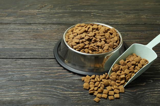 Miska dla zwierząt i miarka z paszą na drewnianym