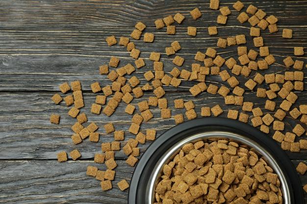 Miska dla zwierząt z karmą na drewnianym