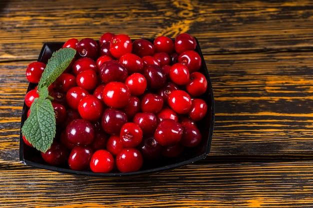 Miska dojrzałych czerwonych wiśni przyozdobionych świeżą miętą na smaczną przekąskę lub do użytku jako składnik do gotowania i pieczenia, widok z góry na drewnianym stole z copyspace