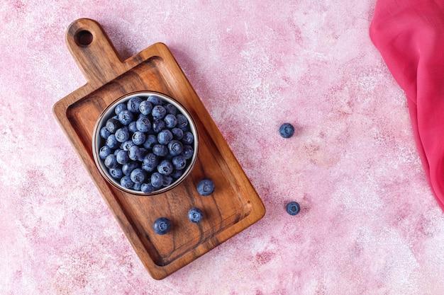 Miska dojrzałych świeżych jagód na drewnianej desce do krojenia