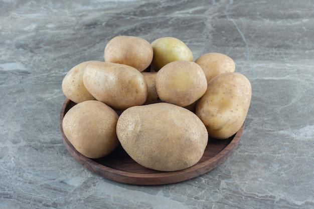 Miska dojrzałych ziemniaków na marmurowym stole.