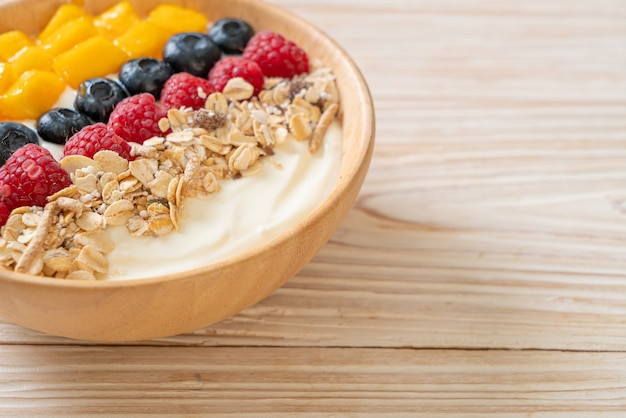Miska domowego jogurtu z malinami, jagodami, mango i granolą - zdrowy styl jedzenia