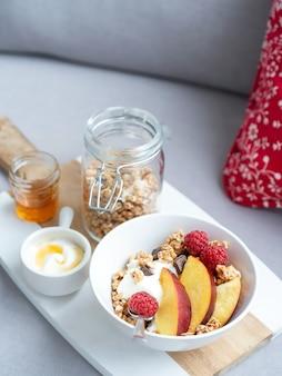 Miska domowej muesli z jogurtem, miodem, świeżymi malinami i nektarynkami