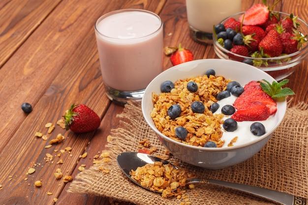 Miska domowej roboty muesli z jogurtem i świeżymi jagodami na drewnianym