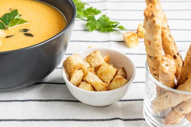 Miska domowej roboty świeżej pikantnej organicznej kremowej zupy z dyni na białym tle włókienniczych paski