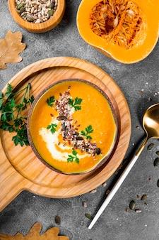 Miska domowej zupy dyniowej z nasionami sezamu i nasionami lnu widok z góry ciepłe jesienne jedzenie