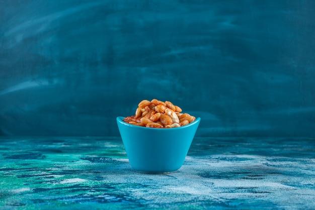Miska fasoli po bretońsku, na niebieskim stole.