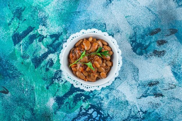 Miska fasoli po bretońsku na podstawce, na niebieskim stole.