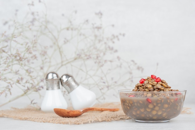 Miska fasoli z nasionami granatu na białym stole