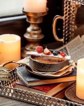 Miska francuskiego deseru przyozdobiona jagodami umieszczonymi na książce