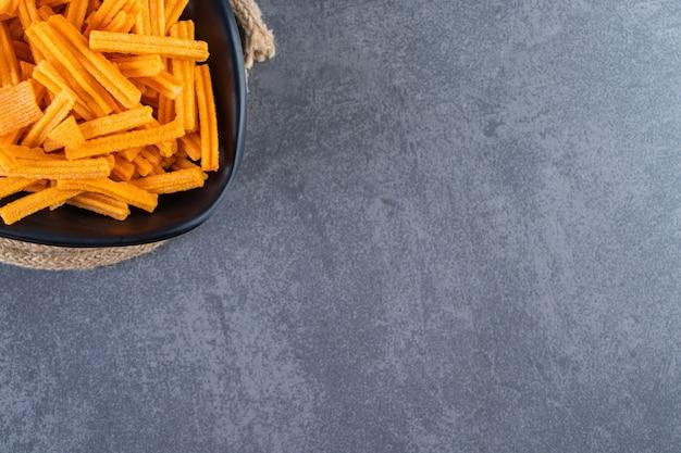 Miska frytek ze słodkich ziemniaków na podstawce na marmurowej powierzchni