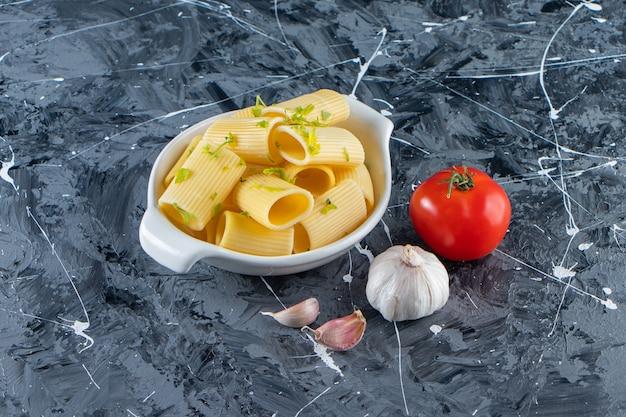 Miska gotowanego makaronu calamarata z warzywami na marmurowej powierzchni.