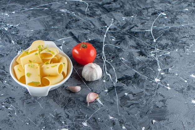 Miska gotowanego makaronu calamarata z warzywami na marmurowym tle.