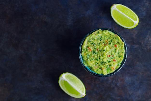 Miska guacamole na ciemnym tle. tradycyjny meksykański sos guacamole. tradycyjne meksykańskie jedzenie. skopiuj miejsce. widok z góry