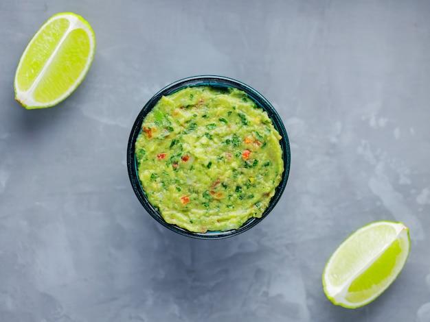 Miska guacamole na szarym tle. tradycyjny meksykański sos guacamole w misce. kuchnia meksykańska. skopiuj miejsce. widok z góry