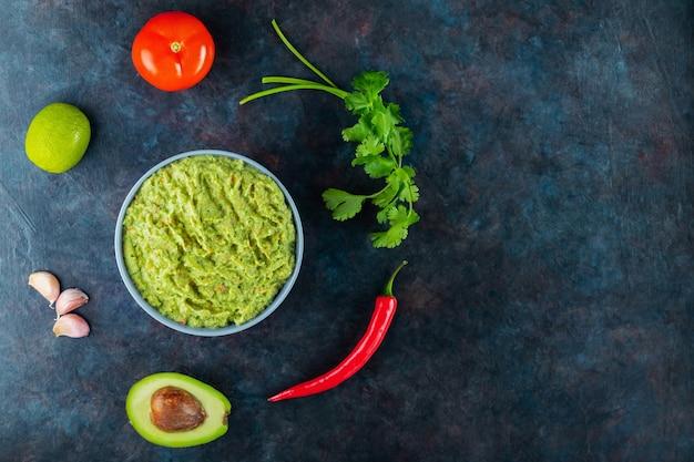 Miska guacamole z dodatkami. sos guacamole i papryczka chili, limonka, awokado, pietruszka, czosnek, pomidor na ciemnym tle. meksykańskie jedzenie. skopiuj miejsce. widok z góry