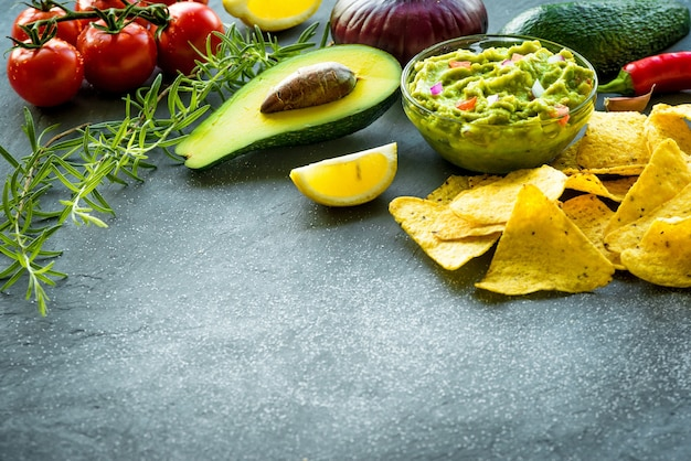 Miska guacamole ze składnikami i chipsami tortilla na kamiennym stole.