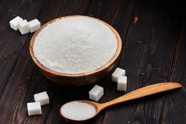 Miska i miarka z białym piaskiem i gęstym cukrem na drewnianym tle