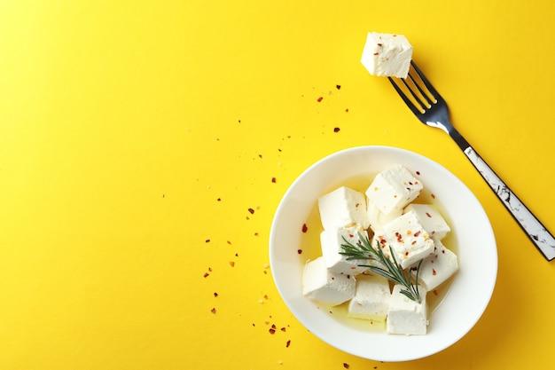 Miska i widelec z serem feta na żółtej powierzchni