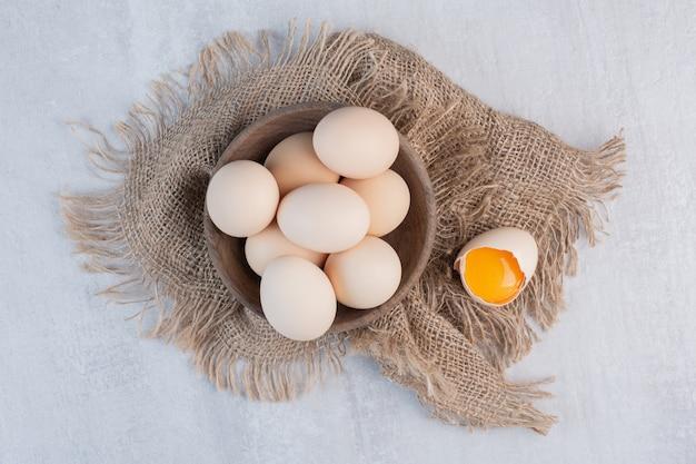 Miska jaj obok żółtka w skorupce na kawałku materiału na marmurowym stole.