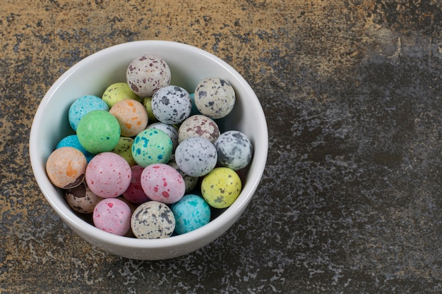 Miska kolorowych cukierków na marmurze.