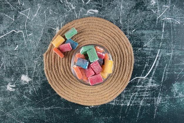 Miska kolorowych cukierków na trójnogu, na stole mieszanym.