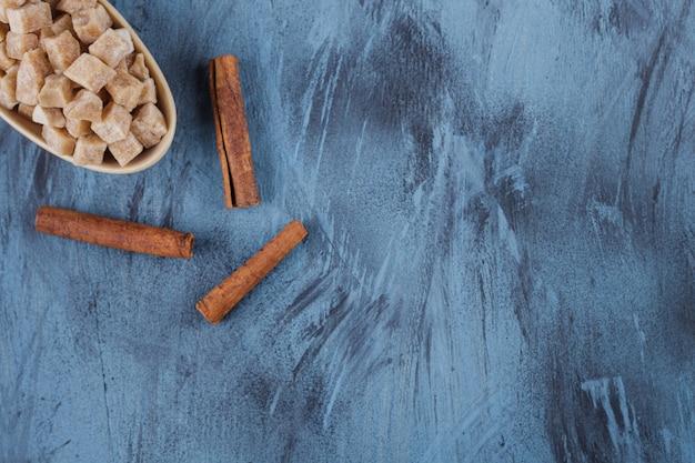 Miska kostek cukru brązowego i laski cynamonu na niebieskiej powierzchni.