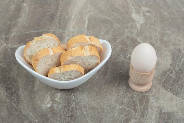 Miska kromek chleba i jajka na marmurze. wysokiej jakości zdjęcie