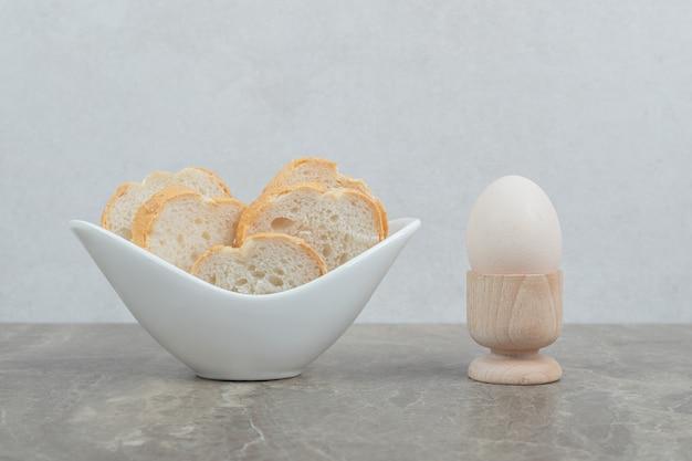 Miska kromki chleba i jajko na marmurowym stole. wysokiej jakości zdjęcie