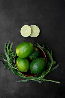 Miska limonki z pokrojonymi limonkami i estragonem na czarnej powierzchni