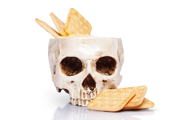 Miska ludzkiej czaszki z sosem serowym i krakersami na białym tle