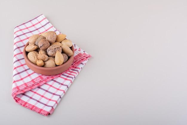 Miska łuskanych organicznych migdałów i orzechów włoskich na białym tle. zdjęcie wysokiej jakości